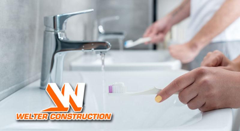two people brushing teeth in morning at sinks